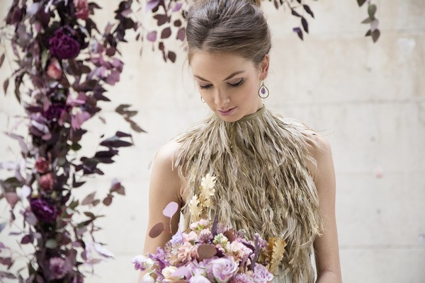 Bride with feather collar bridal neckpiece looking down at purple bouquet