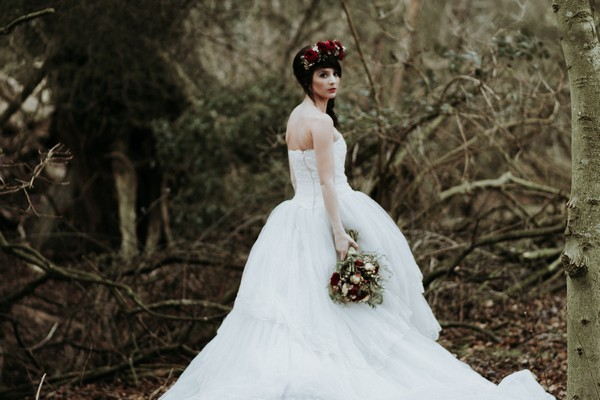 Bride holding bouquet in woodland