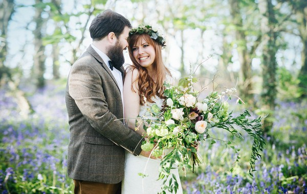 Bride and groom in woodland with bluebells