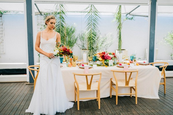 Bride with colourful bouquet standing next to wedding table with tropical styling