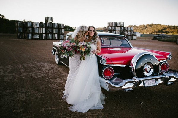 Two brides in front of a vintage Ford wedding car