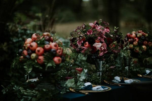 Three foliage and fruit displays on wedding table