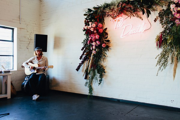 Acoustic guitarist playing in wedding ceremony room at Gather and Tailor
