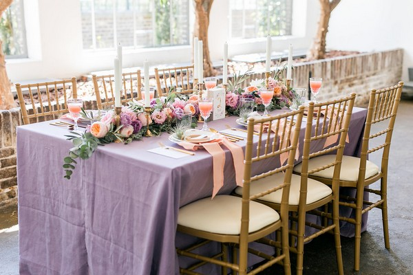 Wedding table with violet tablecloth and peach details