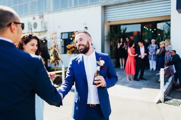 Groom welcoming guests to wedding