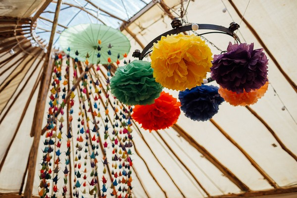 Colourful pom poms hanging in wedding marquee