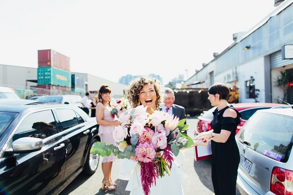 Happy bride carrying large bouquet