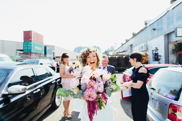 Happy bride carrying large bouquet