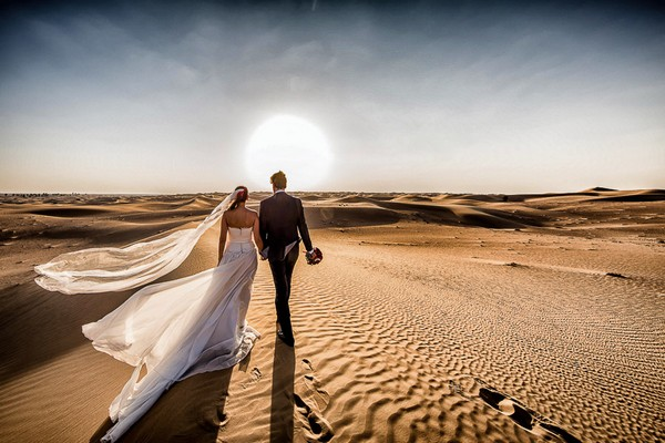 Bride and groom walking across desert towards the sun - Picture by Cristiano Ostinelli Studio