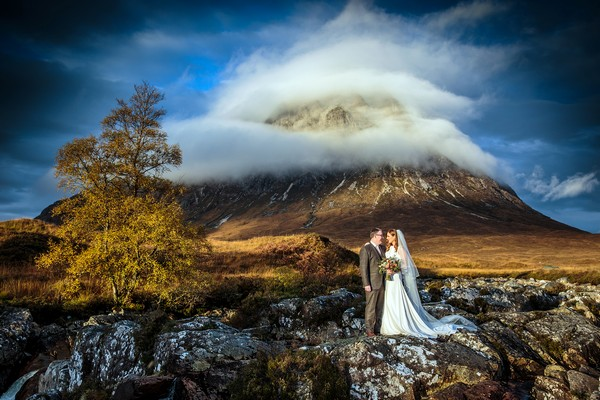 Bride and groom in front of Glencoe hill surrounded by clouds - Picture by Stuart Craig Photography