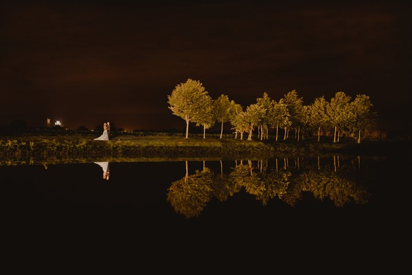 Bride and groom standing by lake at night with trees reflecting in the water - Picture by Lee Allison Photography