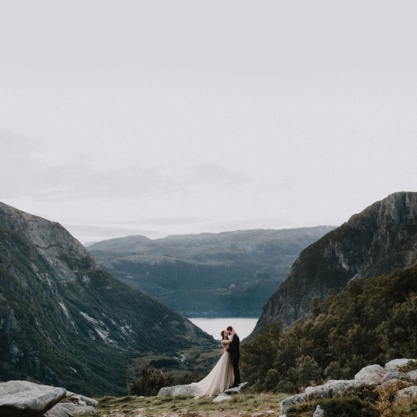 Bride and groom kissing with mountains in the background - Picture by Iskra Photography