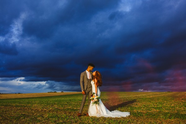 Bride and groom looking at each other with dark blue clouds behind them - Picture by Clare Tam-Im Photography