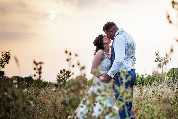 Bride and groom kissing in a field - Picture by Kevin Lines Photography