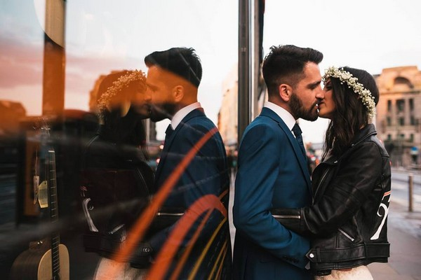 Bride and groom kissing against window showing their reflection - Picture by Fiona Higgins Photography