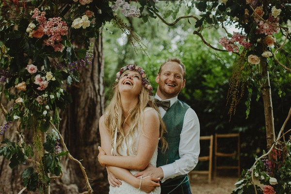 Groom and bride with flower crown laughing under floral arch - Picture by The Curries