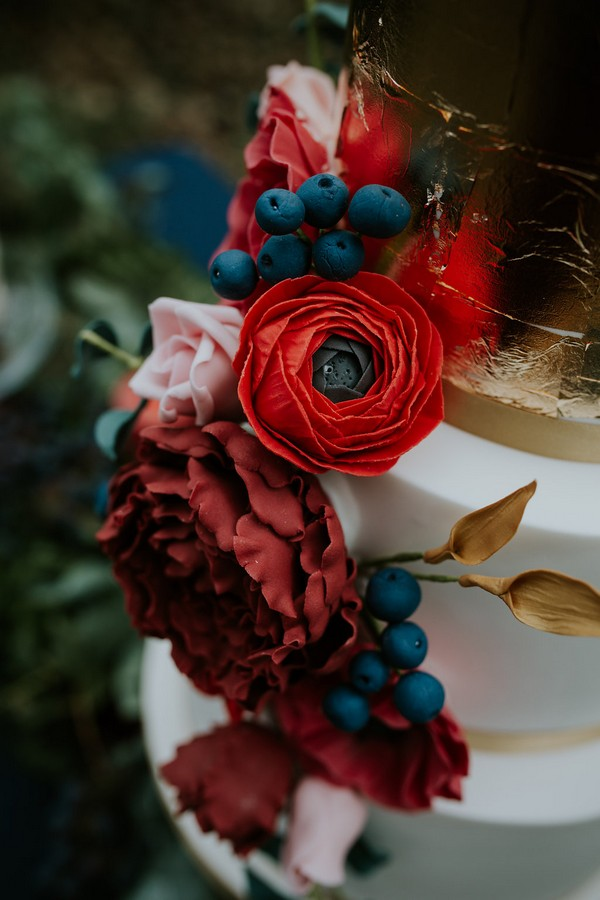 Red flower and berry wedding cake decoration