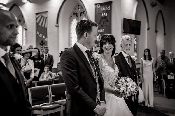 Bride and groom smiling at each other at the altar