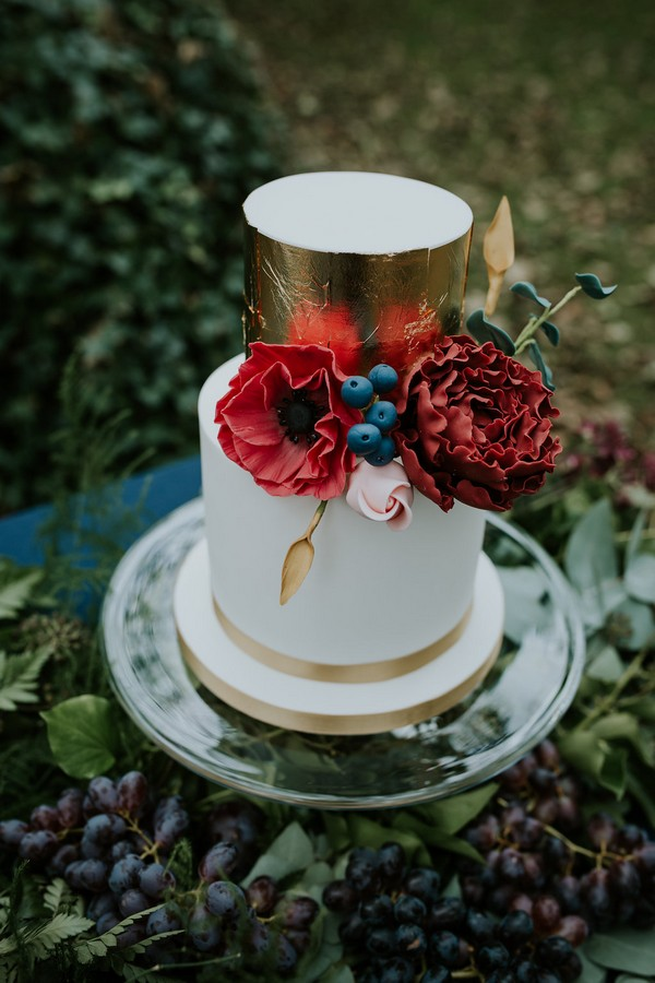 White and gold wedding cake with red flowers