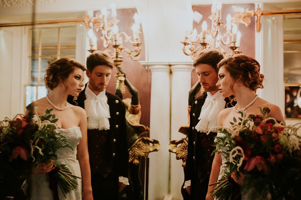Bride and groom in Poldark style clothing standing in front of a mirror