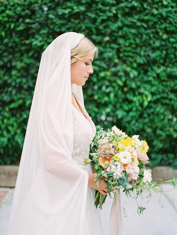 Side on view of bride holding bouquet