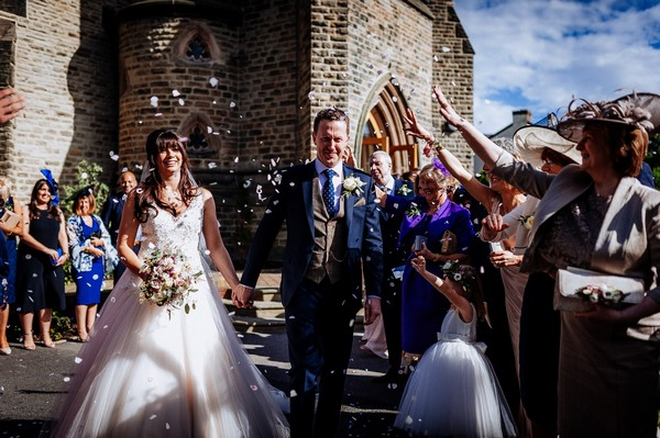 Wedding guests throwing confetti over bride and groom