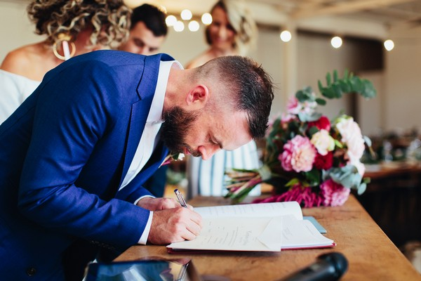 Groom signing marriage register