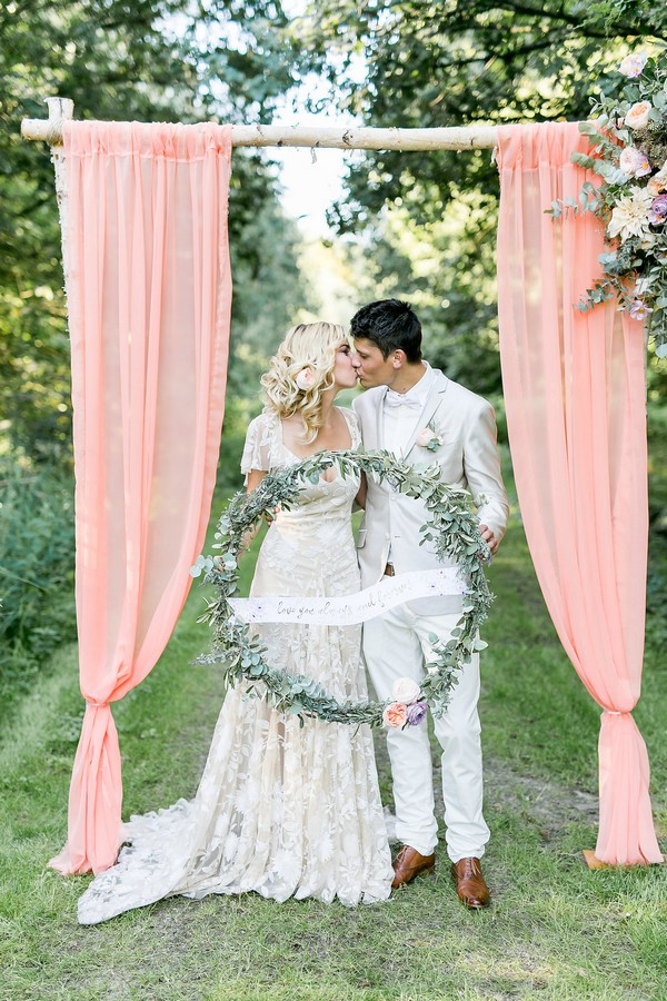 Bride and groom kissing holding large wreath