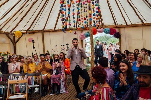 Groomsman dancing in to wedding ceremony