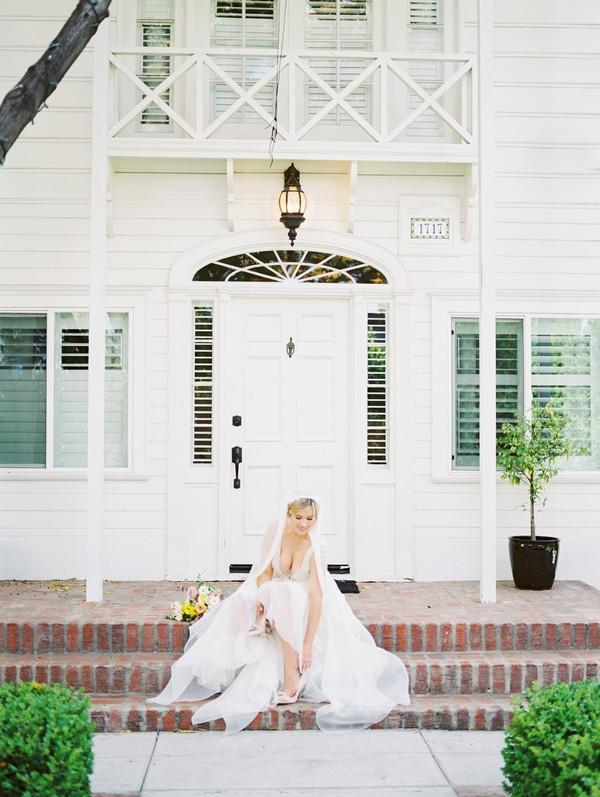 Bride sitting on steps of Lombardi House