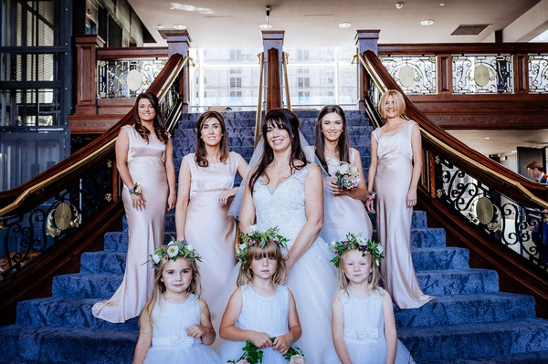 Bride, bridesmaids and flower girls on stairs inside Titanic Hotel Liverpool