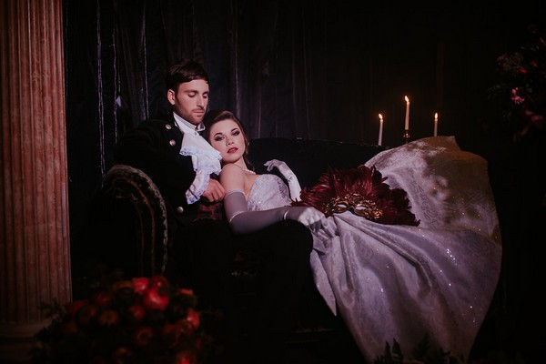 Bride leaning back on groom as they sit on couch