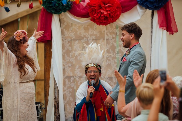 Celebrant enthusiastically announcing bride and groom as husband and wife
