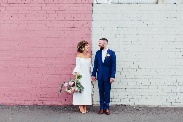 Bride and groom standing against pink and white wall