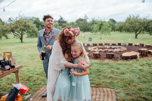 Bride hugging flower girls