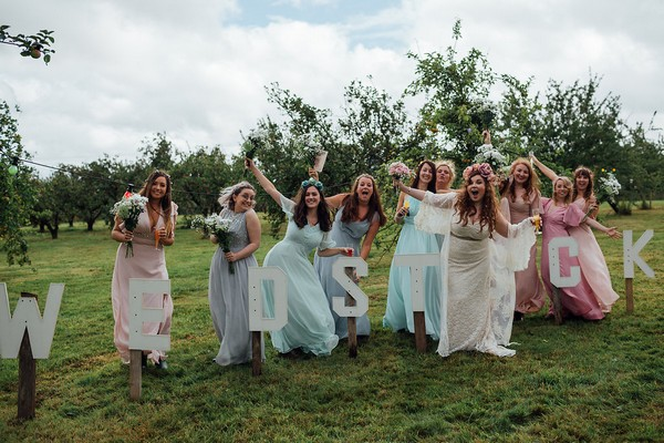Bride and bridesmaids posing by Wedstock sign