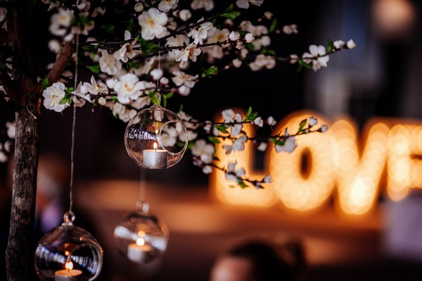 Tea light in bauble hanging from tree