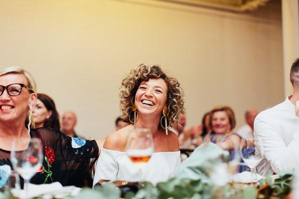 Bride smiling as she listens to wedding speech