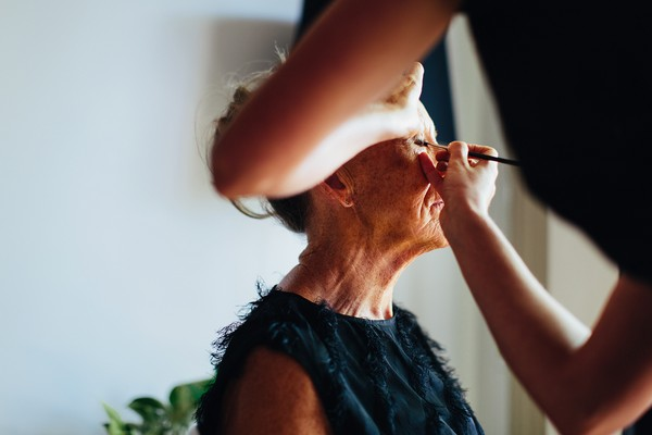 Woman having make-up done before wedding