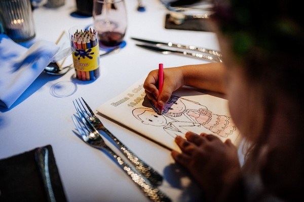 Child colouring in wedding activity book