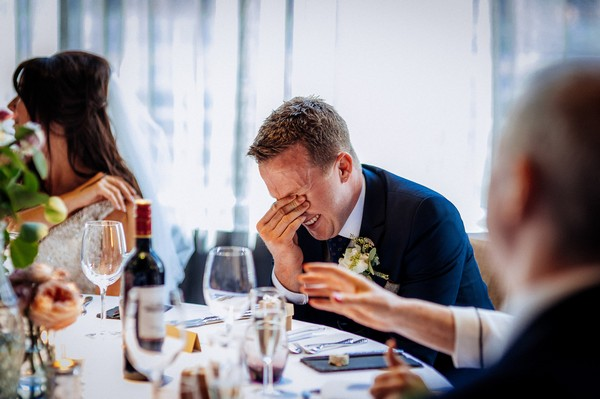 Groom with hand over his eyes as he listens to best man speech