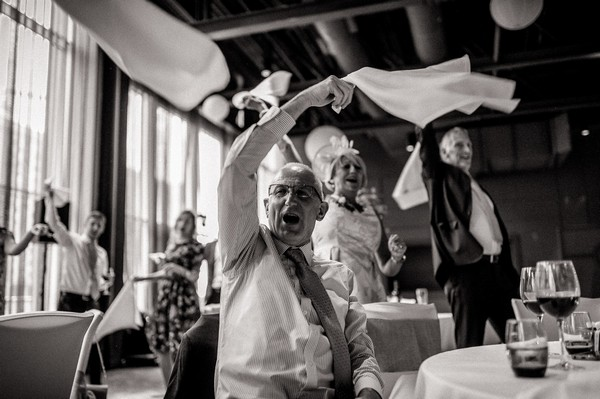 Wedding guests waving napkins over their heads