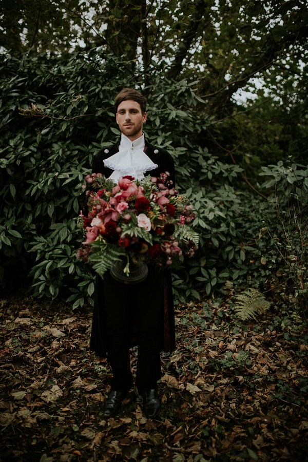 Groom in Poldark clothing holding large bouquet