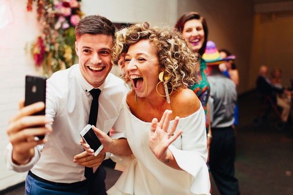 Bride and wedding guest taking selfie