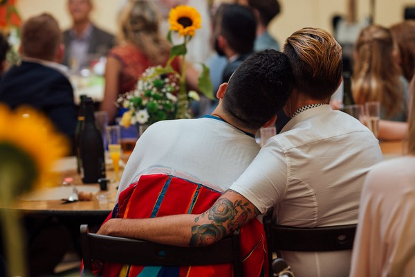 Guests with arms around each other as they listen to wedding speeches