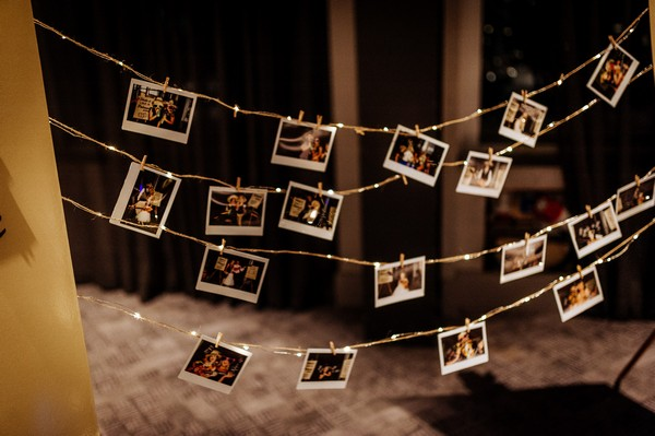 Photo booth pictures pegged to fairy lights