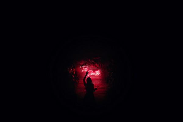Til Death sign lit up in dark room