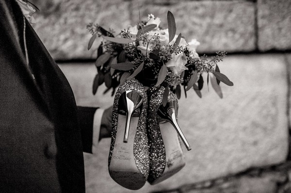 Groom carrying bride's shoes and bouquet