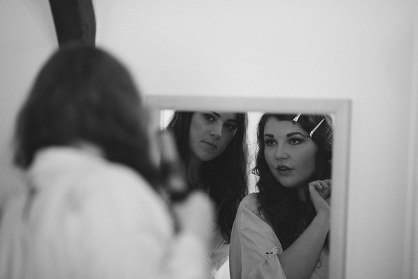 Bride and bridesmaid looking in mirror getting ready