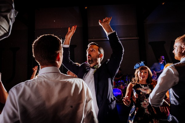 Wedding guests with arms in the air